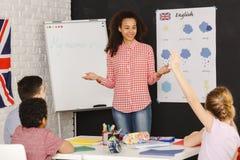 Crianças de ensino da jovem mulher imagem de stock royalty free