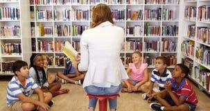 Crianças de ensino do professor na biblioteca filme