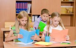 Crianças de escola primária nos livros de leitura da sala de aula Fotografia de Stock
