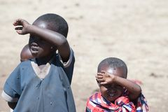 Crianças de Maasai com os olhos completos das moscas, Tanzânia As moscas colocam ovos nos olhos de modo que a criança pudesse ir  imagem de stock