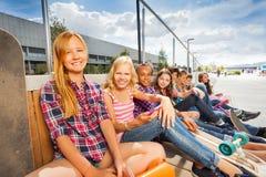 Crianças de relaxamento felizes que sentam-se na construção de madeira Fotografia de Stock Royalty Free