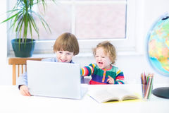 Crianças de riso engraçadas que jogam junto com um portátil imagens de stock