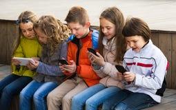 Crianças de riso que sentam-se com dispositivos móveis imagem de stock