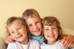 Crianças de riso três junto no quarto cosy imagens de stock royalty free