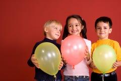 Crianças de sorriso com ballons Fotografia de Stock