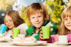 Crianças de sorriso com os copos de chá que sentam-se fora Fotografia de Stock