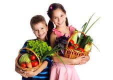 Crianças de sorriso com os vegetais na cesta Fotos de Stock Royalty Free