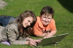 Crianças de sorriso com um portátil Fotografia de Stock