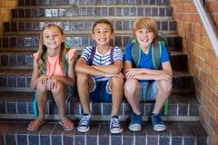 Crianças de sorriso da escola que sentam-se junto na escadaria imagem de stock