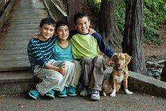 Crianças de sorriso e um cão Fotos de Stock Royalty Free