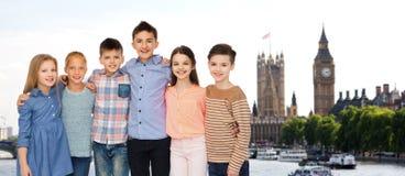 Crianças de sorriso felizes que abraçam sobre Londres Imagens de Stock