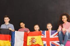 Crianças de sorriso que guardam bandeiras imagens de stock royalty free
