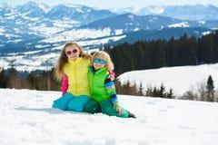 Crianças de sorriso que jogam com neve em montanhas do inverno em um sol Fotografia de Stock