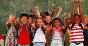Crianças de sorriso que mostram os polegares acima na sala de aula filme