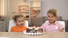 Crianças de sorriso que olham o bolo de chocolate na tabela, felicidade da infância, presente filme