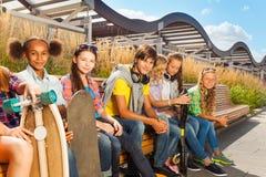 Crianças de sorriso que se sentam no banco de madeira junto Imagens de Stock Royalty Free