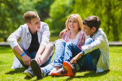 Crianças de sorriso que têm o divertimento na grama Crianças que jogam fora no verão os adolescentes comunicam exterior Imagens de Stock