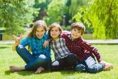 Crianças de sorriso que têm o divertimento na grama Crianças que jogam fora no verão os adolescentes comunicam exterior Imagem de Stock Royalty Free