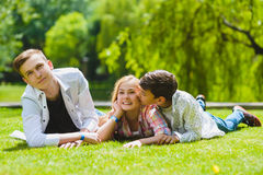 Crianças de sorriso que têm o divertimento na grama Crianças que jogam fora no verão os adolescentes comunicam exterior Fotografia de Stock Royalty Free
