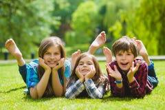 Crianças de sorriso que têm o divertimento na grama Crianças que jogam fora no verão os adolescentes comunicam exterior Fotos de Stock Royalty Free