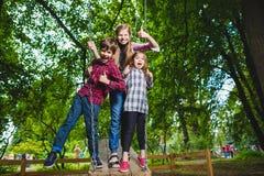 Crianças de sorriso que têm o divertimento no campo de jogos Crianças que jogam fora no verão Adolescentes que montam em um balan Imagem de Stock Royalty Free