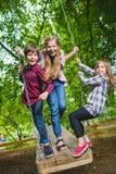 Crianças de sorriso que têm o divertimento no campo de jogos Crianças que jogam fora no verão Adolescentes que montam em um balan Fotos de Stock Royalty Free