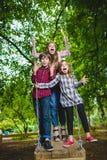 Crianças de sorriso que têm o divertimento no campo de jogos Crianças que jogam fora no verão Adolescentes que montam em um balan Imagem de Stock
