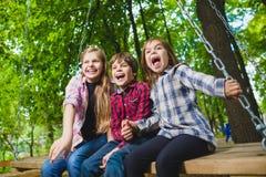 Crianças de sorriso que têm o divertimento no campo de jogos Crianças que jogam fora no verão Adolescentes que montam em um balan Fotografia de Stock Royalty Free