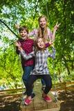 Crianças de sorriso que têm o divertimento no campo de jogos Crianças que jogam fora no verão Adolescentes que montam em um balan Imagens de Stock Royalty Free