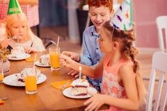 Crianças deleitadas positivas que discutem o gosto do bolo imagens de stock royalty free