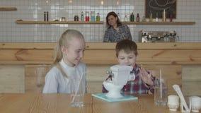 Crianças despreocupadas alegres que jogam o brinquedo na tabela do café video estoque