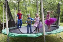 Crianças disfarçadas como os super-herói ou as princesas que saltam no trampolim Fotos de Stock Royalty Free