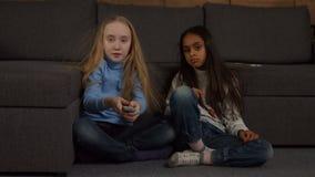 Crianças diversas adoráveis que olham a tevê em casa video estoque