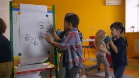 Crianças diversas alegres que pintam handprints na classe filme