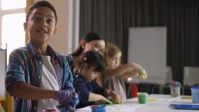 Crianças diversas bonitos que pintam com mãos na lição video estoque
