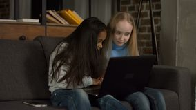 Crianças diversas que surfam a rede no portátil em casa vídeos de arquivo