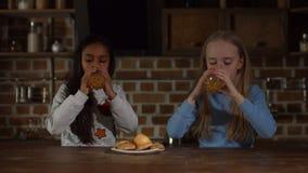 Crianças diversas relaxado que bebem o suco na cozinha filme