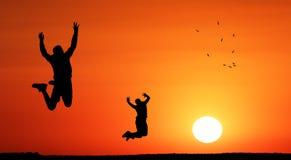 Crianças do adolescente que saltam no por do sol para a liberdade imagem de stock royalty free