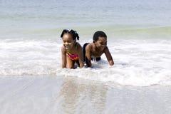 Crianças do americano africano que jogam na praia Foto de Stock