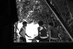 Crianças do Fijian que sentam-se no banco que fala através da janela imagens de stock