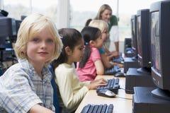 Crianças do jardim de infância que aprendem usar computadores Fotografia de Stock