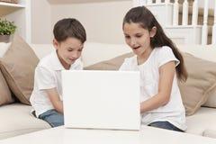Crianças do menino & da menina que usam o computador portátil em casa Fotografia de Stock Royalty Free