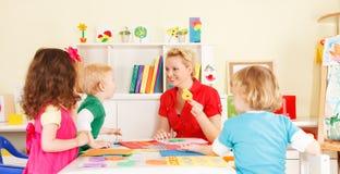 Crianças do pré-escolar na sala de aula com o professor foto de stock