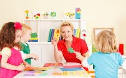 Crianças do pré-escolar na sala de aula com o professor foto de stock royalty free