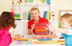 Crianças do pré-escolar na sala de aula com o professor imagens de stock