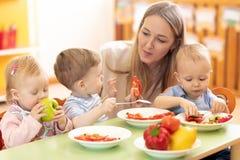 Crianças do professor e da criança em idade pré-escolar que têm a ruptura para frutos fotografia de stock