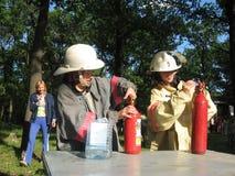 Crianças do treinamento em habilidades da luta contra o incêndio em um acampamento de verão É útil na vida fotografia de stock