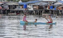 Crianças do tribo de Bajau que têm o divertimento enfileirando o bote perto de suas casas da vila no mar, Sabah Semporna, Malásia foto de stock