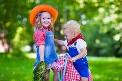 Crianças do vaqueiro que jogam com cavalo do brinquedo Fotografia de Stock Royalty Free