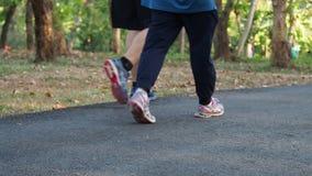 Crianças dos povos, adulto, pessoa idosa que corre, movimentando-se e para andar em público o parque para eles corpo forte acima  filme